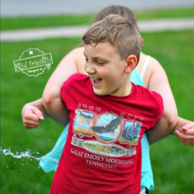 Two kids squeezing a water balloon between their backs