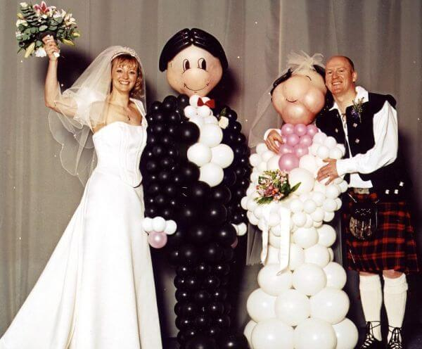 Bride and groom balloon sculptures, made with round latex balloons.