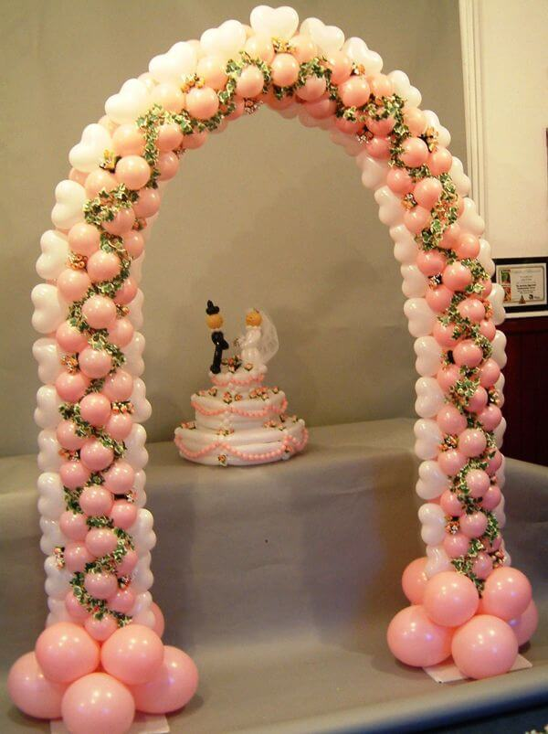 Cake table balloon arch in rose and white.
