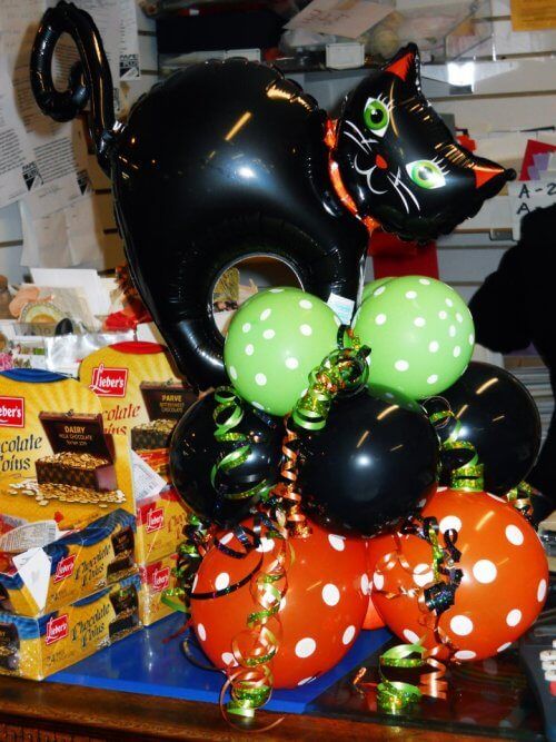 Cute Halloween balloon decor with a black cat on top.