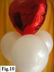 Arranging the three mylar balloons at the same height below the mylar heart.