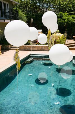 Large round balloons floating in pool (Source: stylemepretty.com)