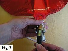 Inserting helium tank nozzle into mylar balloon valve.