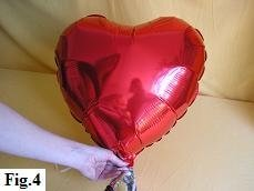 Inflating mylar balloon heart with helium.