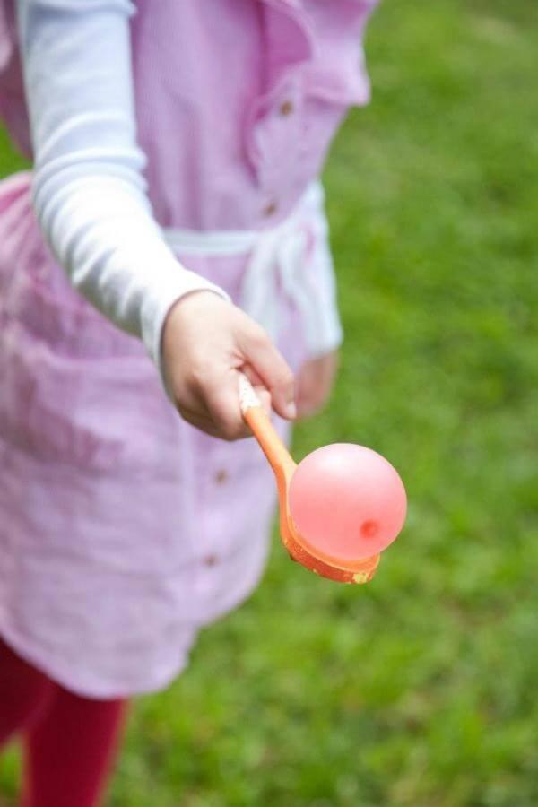 Girl balances water balloon on a spoon