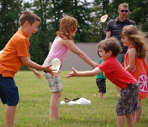 Kids playing water balloon toss
